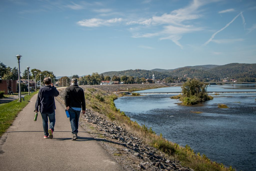 Two people walk on the Lock Haven river walk along West Branch Susquehanna River