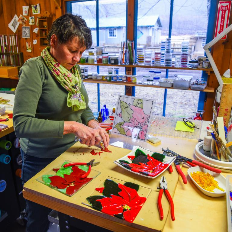 Fused glass artist Kathleen Schnell works on a project
